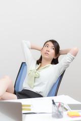 机に足をのせて考える女性