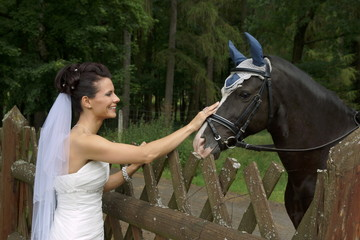 Young bride stroking horse in forest park