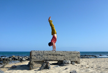 Man Handstands on top a old pillbox on the beach
