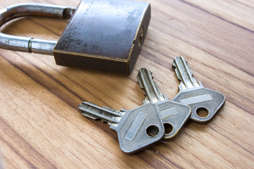 Padlock with keys on wooden