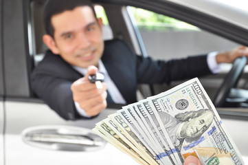 Businessman giving a car key exchanging with money - car pawn