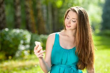 Красивая молодая девушка на природе с сотовым телефоном
