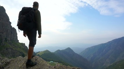 Young man standing on top of a rock high in the mountains