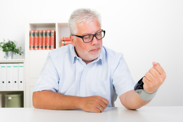 mann prüft blutdruck am handgelenk