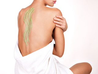 woman cares about skin of body using cosmetic scrub on the back
