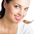 Woman eating muesli or cornflakes, isolated