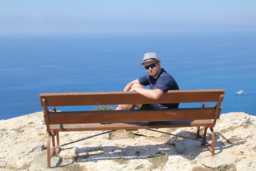 guy sits on a bench on Greco's cape, Cyprus