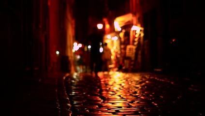People walking on dark street at night.
