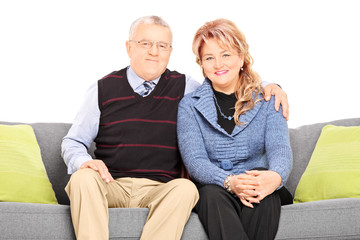 Mature couple posing seated on a couch