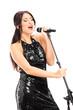 Elegant female singer singing on microphone