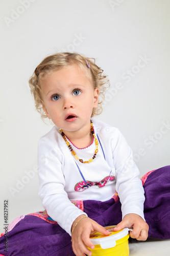 canvas print picture kleines Mädchen spielt mit Plastik Dose
