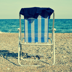 deckchair and man swimsuit on the beach, with a retro effect