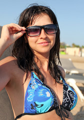 Photo of sexy tanned woman with sun glasses on the beach