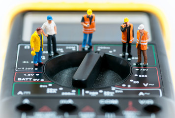 Team of miniature workers on top of multimeter. Macro photo