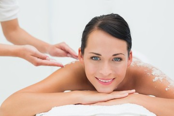 Peaceful brunette getting a salt scrub beauty treatment
