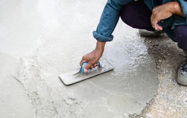 Man's plastering a floor with trowel. Construction worker