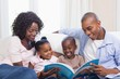 Happy family on the couch reading storybook