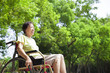 Asian senior woman sitting on a wheelchair in the park