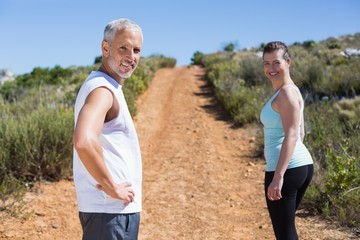 Fit smiling couple jogging up mountain trail