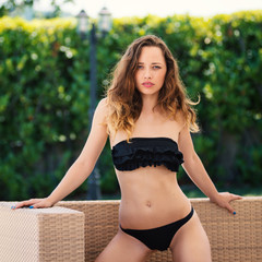 Sensual woman portrait wearing black bikini posing outdoors.
