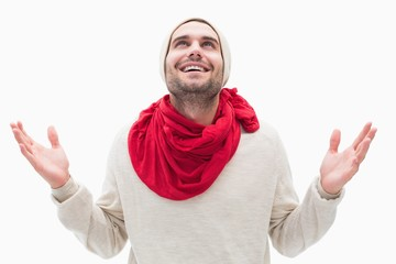 Attractive young man in warm clothes with hands up