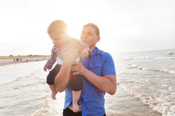 Young father holding his child on the beach having fun together