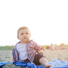 Handsome curious child sitting on the beach looking at the sky