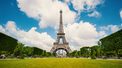 Eiffel Tower and gardens with people walking against blue cloudy