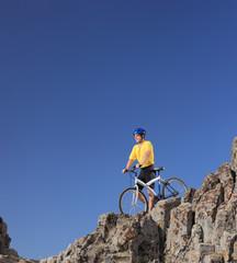 Mountain biker standing on a rocky cliff