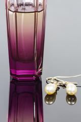 Parfum bottle and pearl earrings.