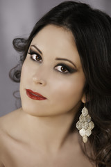 Sensual brunette woman with red lips and earring