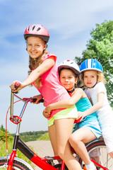 Close up view of three girls on bike