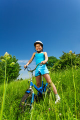 Little smiling girl sitting on a bicycle