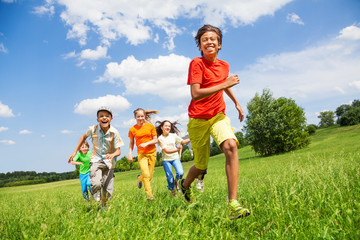 Happy children running together in the field