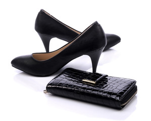 Women's shoes and a black wallet on a white background