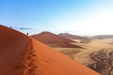 People on sunrise dunes of Namib desert, South Africa