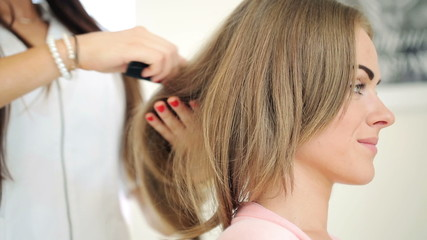Hairdresser combing hair of female client in hair salon