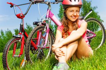 Little girl in red helmet sits on a meadow
