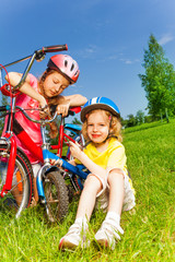 Two little girls fixing bicycles