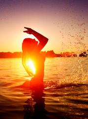 Teen girl swimming and splashing on summer beach over sunset