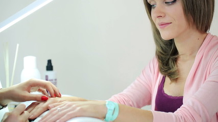 Woman painting finger nails in beauty salon