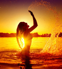 Teen girl swimming and splashing on summer beach over sunset