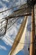 Tall ship mast and sail against blue sky