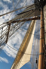 Tall ship mast and sail against blue sky