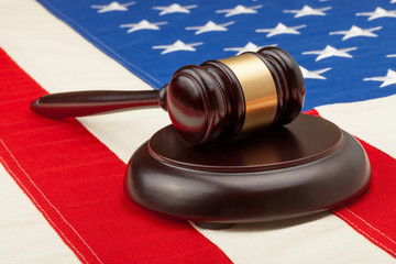 Wooden judge gavel and soundboard laying over USA flag