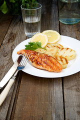 Grilled salmon with potatoes on a white plate\