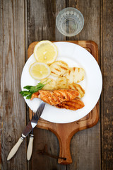 Grilled salmon with potatoes on a white plate