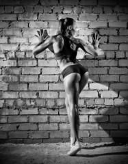 Muscular woman on brick wall (monochrome version)