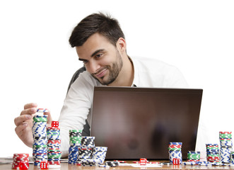 Stacking poker chips while smiling behind labtop