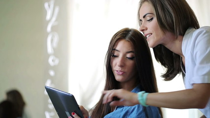 Client choosing haircut on tablet computer in beauty salon